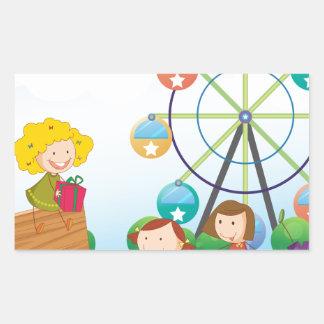 An empty signboard with kids near a ferris wheel rectangular sticker