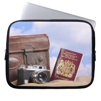 An old leather suitcase, retro camera and laptop sleeve