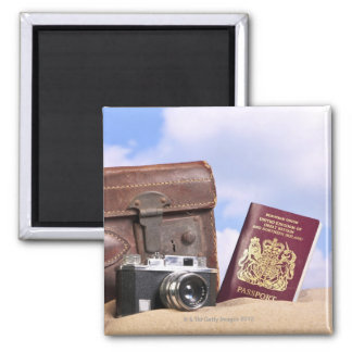 An old leather suitcase, retro camera and magnet