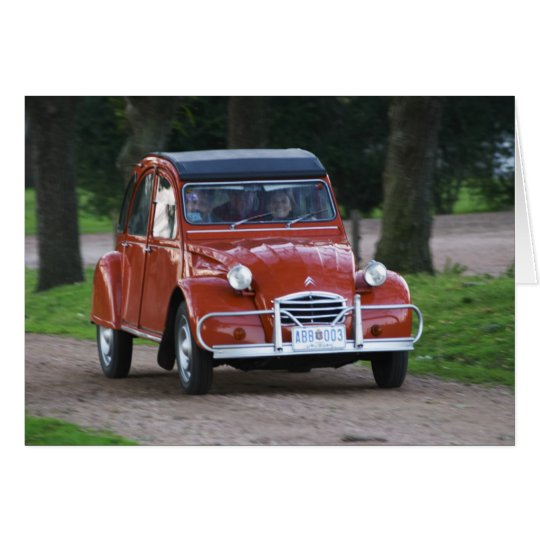 An old red Citroen 2CV car with a