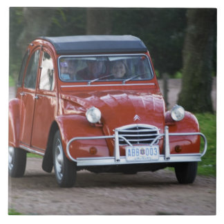 An old red Citroen 2CV car with a smiling woman Large Square Tile