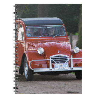 An old red Citroen 2CV car with a smiling woman Notebook