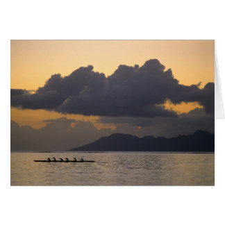 An outrigger canoe team practices off the coast cards