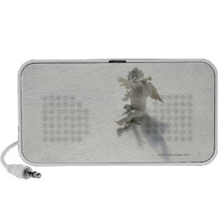 Angel figurine with musical instruments on white notebook speakers