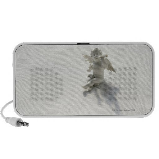Angel figurine with musical instruments on white travelling speakers