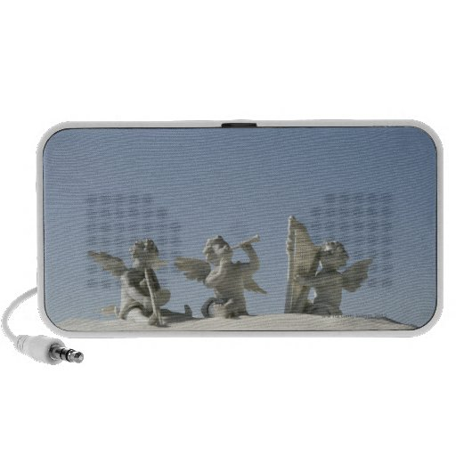 Angel figurines with musical instruments on speaker