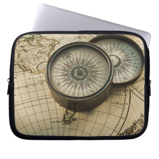 Antique compass on map laptop sleeves