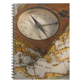 Antique compass on map notebooks