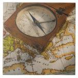 Antique compass on map tile
