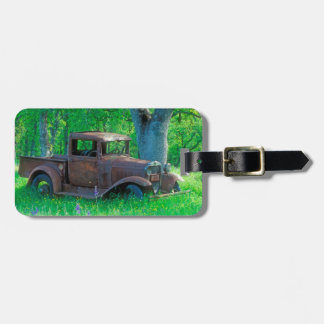 Antique rusted truck in a meadow luggage tag