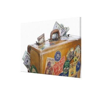 Antique suitcase with protruding money canvas print