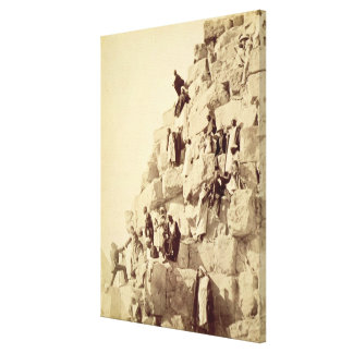 Arabs assisting tourists to climb the pyramids at canvas print