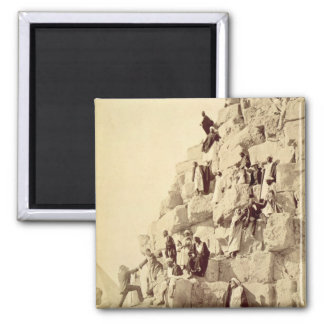 Arabs assisting tourists to climb the pyramids at square magnet