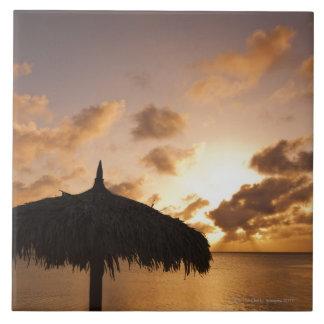 Aruba, silhouette of palapa on beach at sunset tile