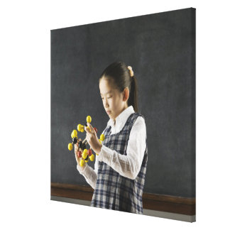Asian girl looking at molecule model canvas print