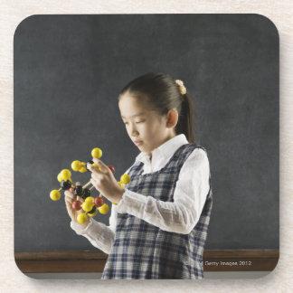 Asian girl looking at molecule model drink coasters