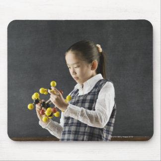 Asian girl looking at molecule model mouse mat