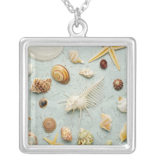Assorted seashells on blue background silver plated necklace