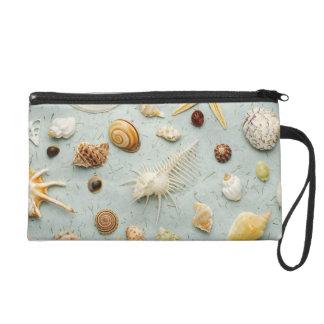Assorted seashells on blue background wristlet purse