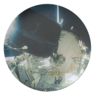 Astronauts Repairing a Satellite in Space Plate