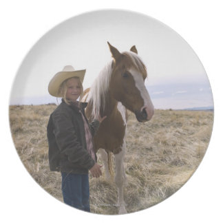 Authentic young cowgirl on range with horse in dinner plates