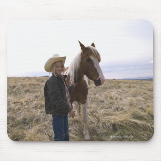 Authentic young cowgirl on range with horse in mouse pad