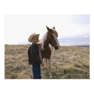 Authentic young cowgirl on range with horse in postcard