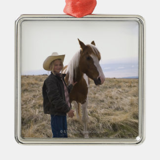 Authentic young cowgirl on range with horse in Silver-Colored square decoration