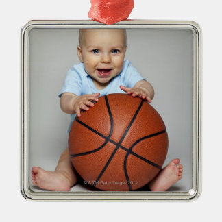 Baby boy (6-9 months) holding basketball, christmas ornament