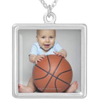 Baby boy (6-9 months) holding basketball, silver plated necklace