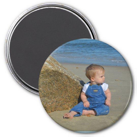 Baby by the ocean pondering. magnet