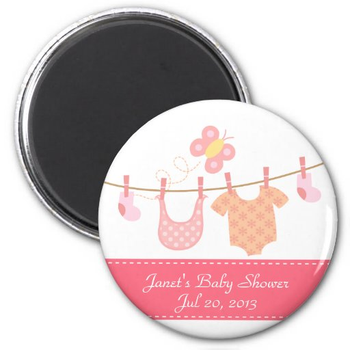 Baby clothes hanging on clothesline with butterfly fridge magnet
