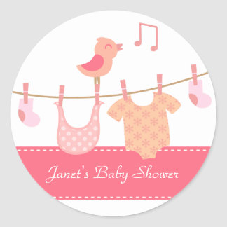 Baby clothes hanging on clothesline with pink bird round sticker