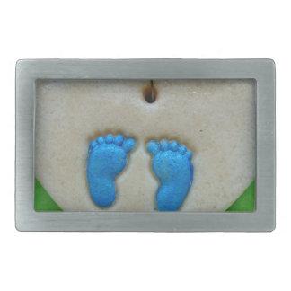 baby feet in blue belt buckles