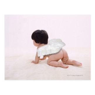 Baby girl in angel wings, smiling, rear view postcard