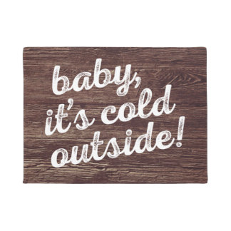 baby, it's cold outside! on dark wood background doormat