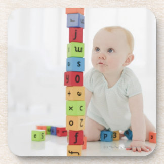 Baby on floor looking at stacked wood blocks coaster