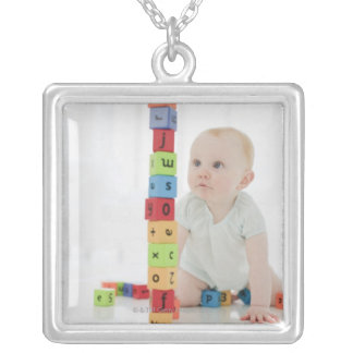 Baby on floor looking at stacked wood blocks silver plated necklace