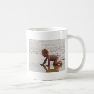 Baby playing in the sand on the beach coffee mug