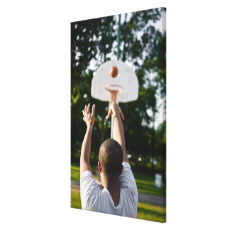 Back view of man shooting basketball outdoors canvas print