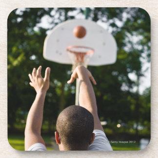 Back view of man shooting basketball outdoors coaster