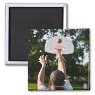 Back view of man shooting basketball outdoors magnet