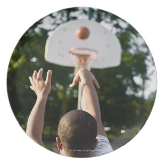 Back view of man shooting basketball outdoors plate