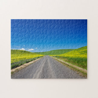 Backcountry road through Spring Canola Fields Jigsaw Puzzle