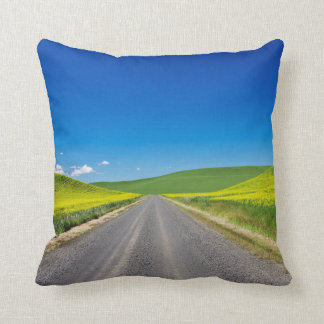 Backcountry road through Spring Canola Fields Throw Pillow