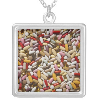 Background of colorful multi-vitamin pills, silver plated necklace