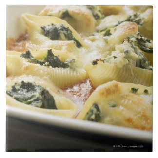 Baked pasta shells with spinach filling large square tile