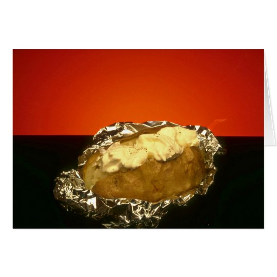 Baked potato with sour cream, against orange backg