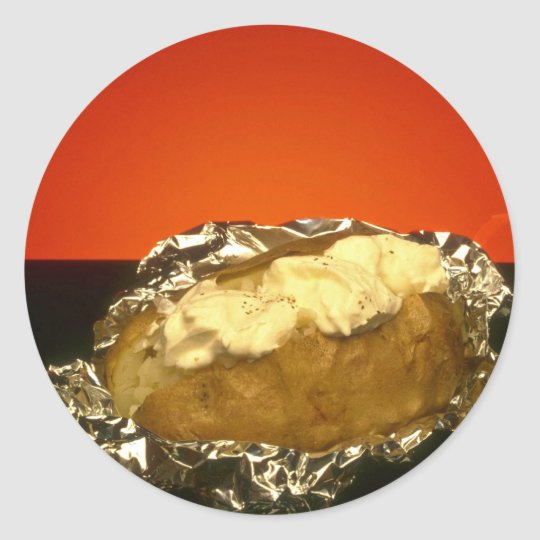 Baked potato with sour cream, against orange backg classic round sticker
