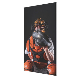 Baseball catcher holding ball in mitt canvas print